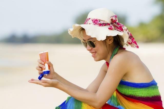 Sunscreen woman. Girl putting sun block on beach holding