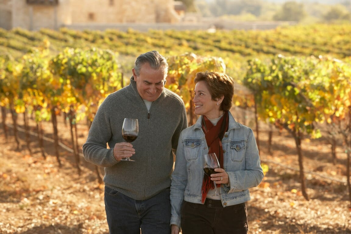 Mature couple standing in vineyard, holding glasses of wine, smiling