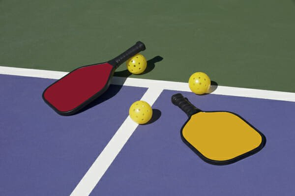 Pickleball - colorful paddles, ball and court