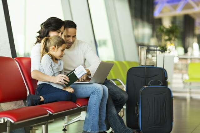 parents and daughter using laptop at airport