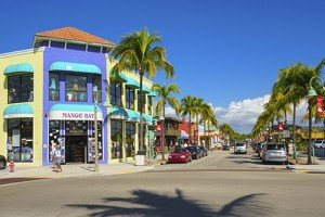 Pedestrians walking past colorful businesses on Old San Carlos Boulevard, in the central shopping and dining district of Fort Myers Beach, Florida.