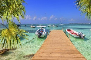 wooden pier and fishing boats on a Caribbean beach with transparent waters
