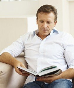 Handsome middle aged man reading a book at home