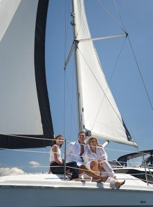 Group of friends having fun on a yacht with blue sky background