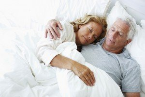 Relaxed elderly couple lying in bed together and sleeping