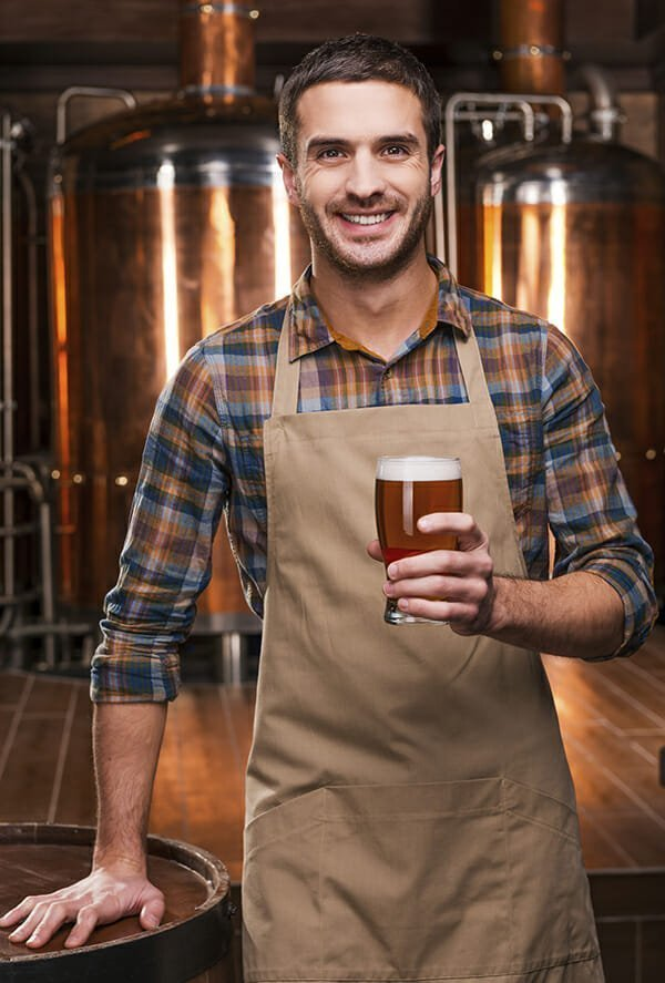 Brewing the best beer. Happy young male brewer in apron holding