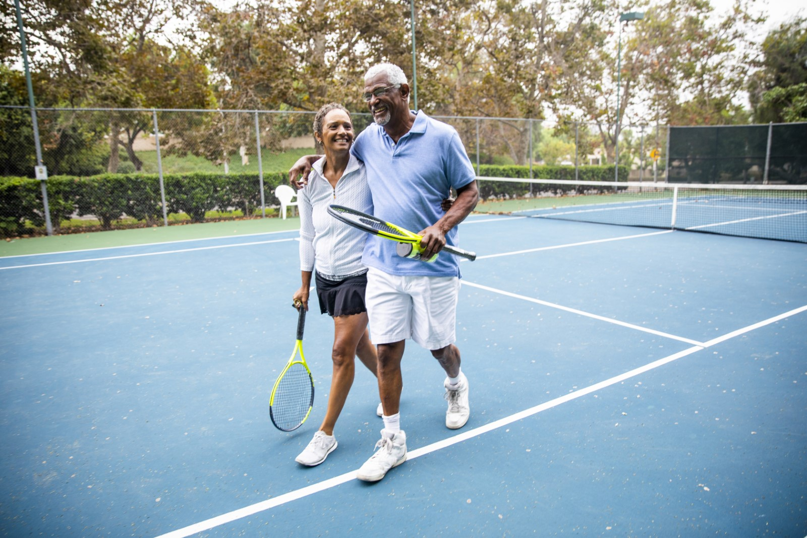 A senior black couple leaving the tennis court after their workout.