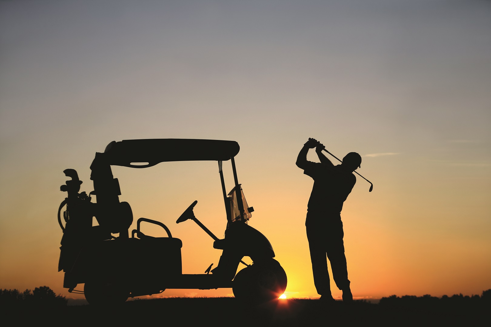 A silhouette of a senior male Caucasian golfer at sunset with powercart. Golfer is demonstrating great form and balance as he swings into a finish position. Image can be used for teaching, golf academy, lessons, senior, retirement, golf resort, golf vacation, back view, athlete, leisure, sports, weekend activities, unrecognizable people, swinging, instruction, and golf cart communities.