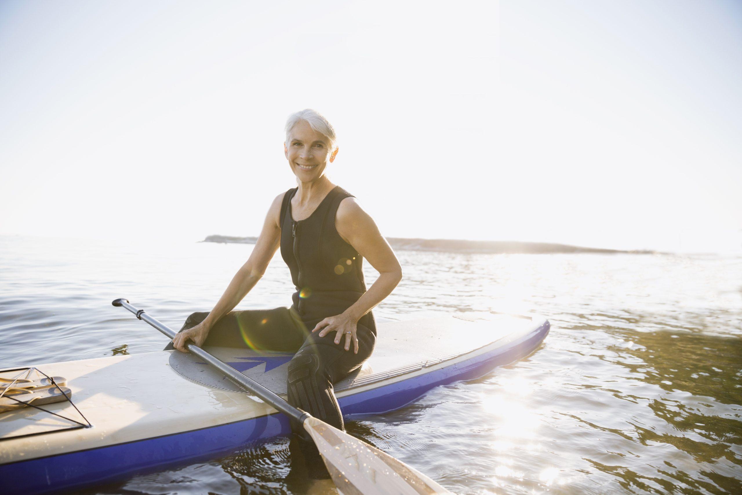 14 Sep 2014 --- Senior woman on paddle board in ocean --- Image by © Hero Images Inc./Hero Images Inc./Corbis