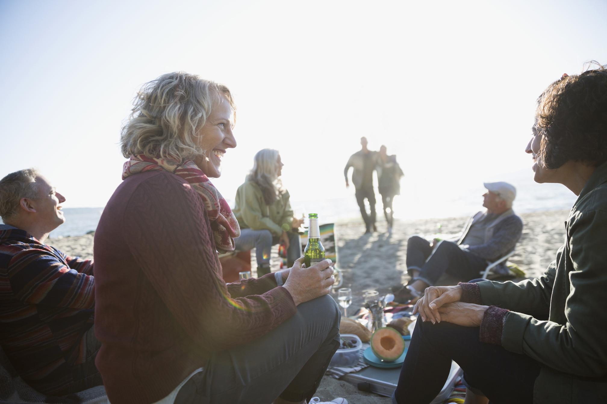 Friends talking and enjoying picnic on sunny beach