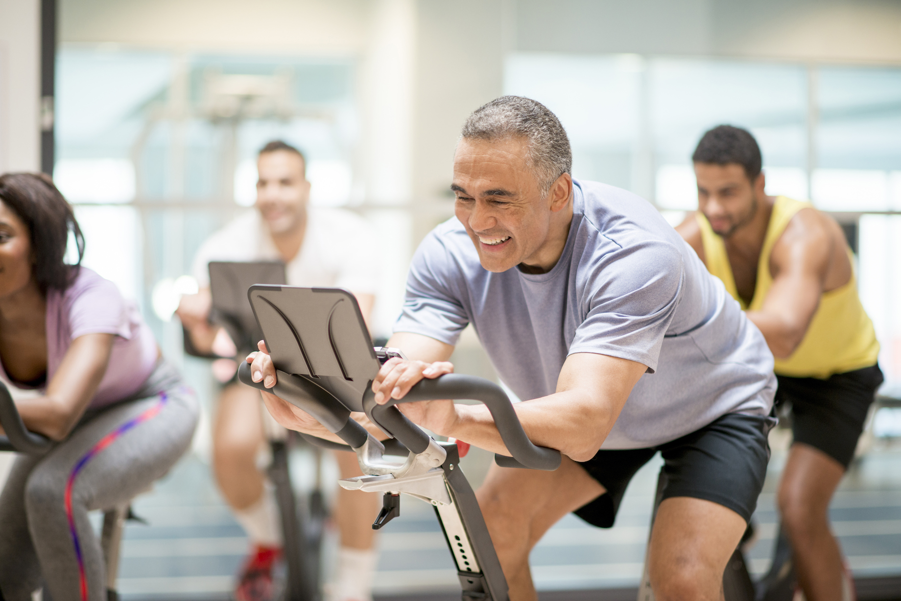 A multi-ethnic group of adults are taking a spin class together at the gym. They are working by cycling on stationary bikes.